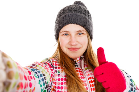 Photo of smiling young girl showing thumbs up