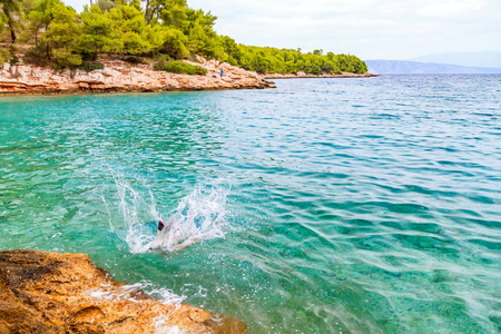 Landscape photo of rocky coastline and tourist jumping in the water Stock Photo