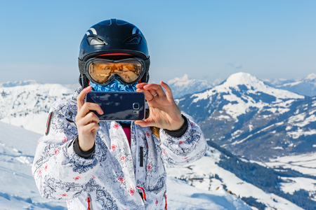 ski area: Young skier woman taking photo with the smartphone