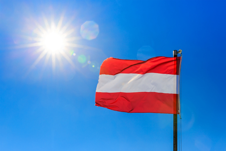 Photo of Austrian flag and sunny clear blue sky