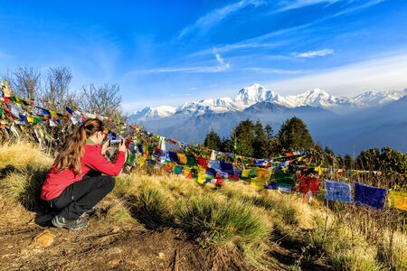 Young tourist taking photos at Poon hill in Nepal