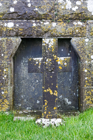 Detail photo of an old cross tombstone