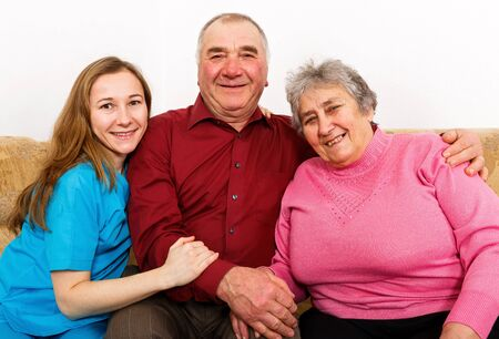 Photo of smiling elderly couple and young caregiver