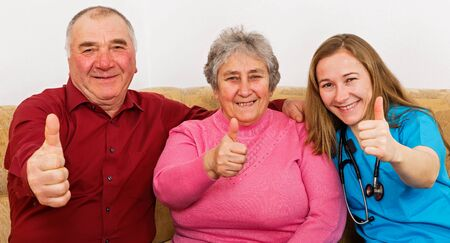 Happy elderly couple and young caregiver showing thumbs up