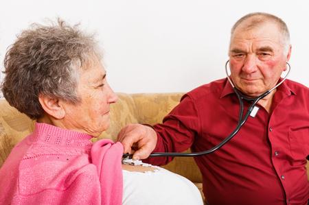 Foto die van bejaarde zijn vrouwenhartslag luistert