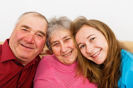 Happy elderly couple and young caregiver smiling for the camera