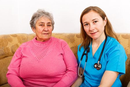 Photo of elderly woman and young caregiver Stock Photo