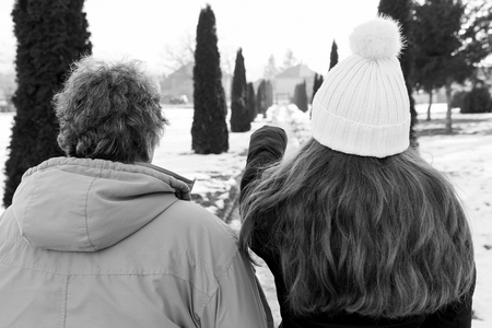 Elderly woman and young caregiver walking in the park in wintertime