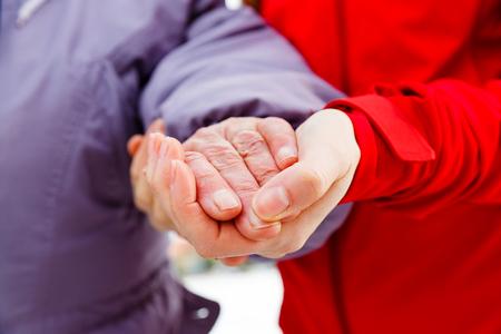 Sluit omhoog foto van jonge verzorger die de bejaardehand houden