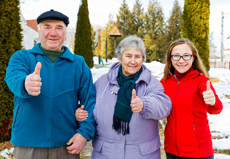 Happy elderly couple and young caregiver showing thumbs up photo