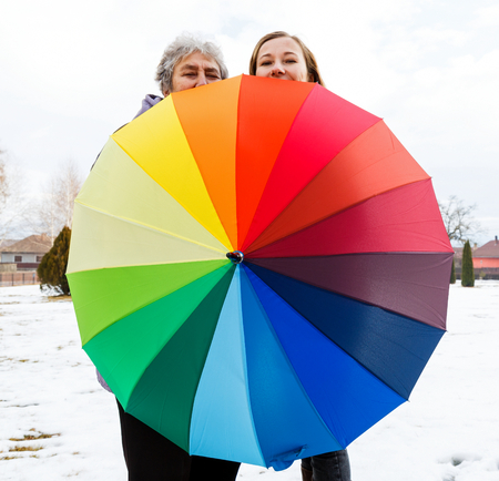 Happy elderly woman and young caregiver walking in the park with colorful umbrella photo