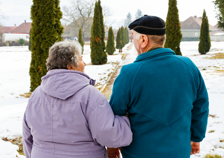 Walking elderly couple in the park in wintertime photo