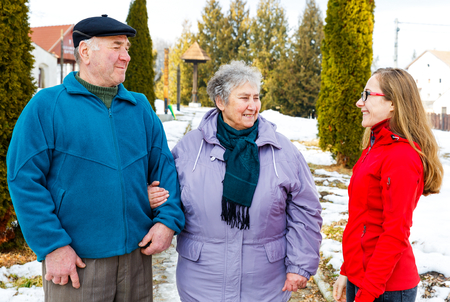 Elderly couple and young caregiver walking in the park in wintertime photo