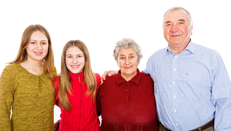 Photo of happy grandparents and granddaughters smiling for the camera Фото со стока