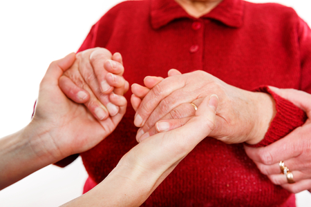 Close up photo of young caregiver holding elderly woman hands