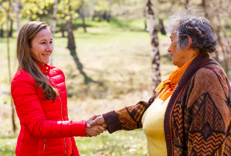 Elderly woman shaking hand with the young caregiver