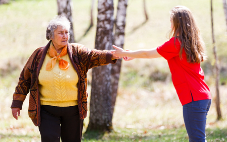Elderly woman and young caregiver walking in the park Stock Photo