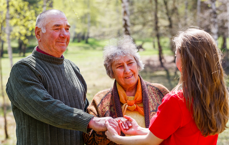 Photo of young caregiver holding elderly couple hands