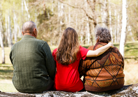 Elderly couple and young caregiver sitting on tree trunk in the park Stock Photo