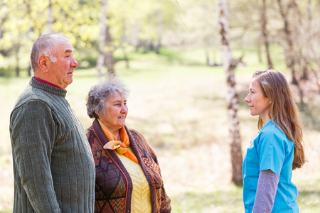 Photo of elderly couple and young caregiver Stock Photo