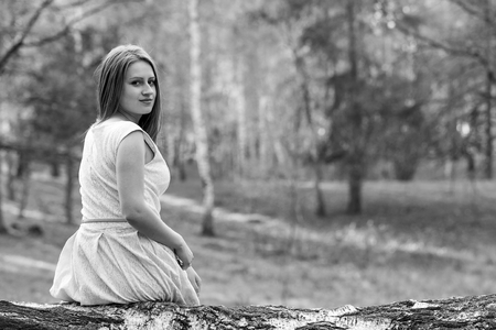 Photo of beautiful young lady sitting on tree trunk in the forest