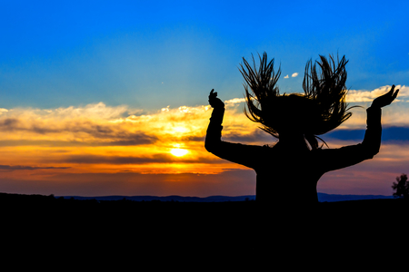 Photo of young woman silhouette in the sunset