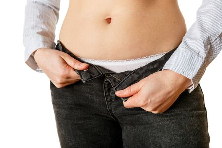 Close up view of woman belly and jeans on white background