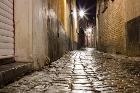 belgie: Oude natte geplaveide straat na regen 's nachts