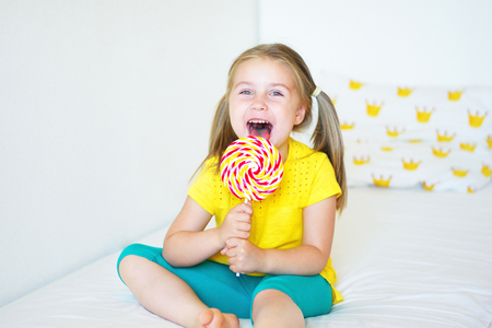 provocative food: Funny child with candy lollipop, happy little girl eating big sugar lollipop, kid eat sweets