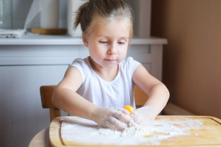 Adorable little girl making the dough for pasta