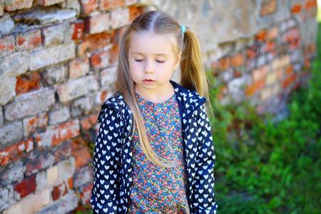 Sad toddler girl standing near brick wall Stock Photo