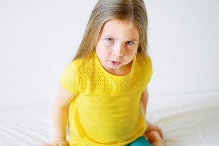 Niña enojada con camiseta amarilla sobre el fondo blanco
