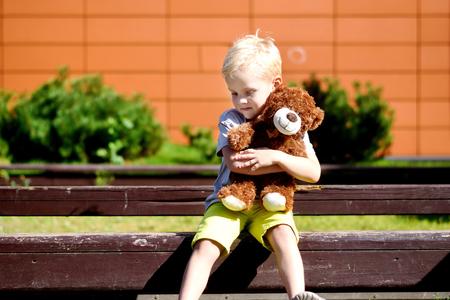 Adorable sad boy with teddy bear in park.