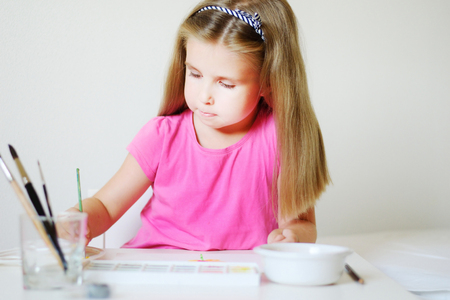 Adorable girl painting with watercolor in a sunny white room at home