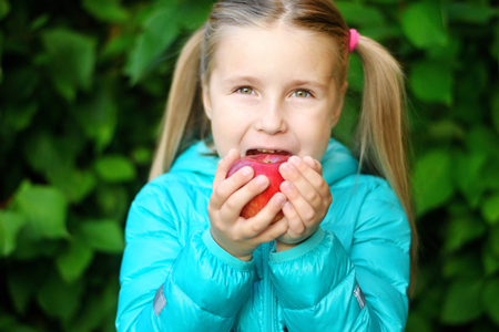 Little girl eating an apple on a wooden bench on autumn day
