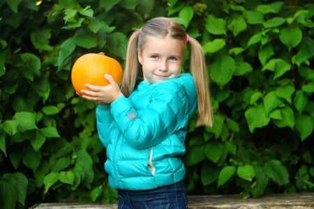 Beautiful smiling girl outdoors holding little pumpkin