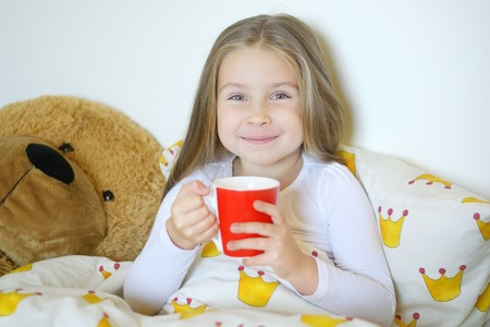 Little girl caught flu and drinking hot tea with lemon in bed