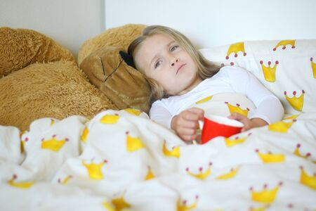 Little girl caught flu and drinking hot tea in bed Stok Fotoğraf