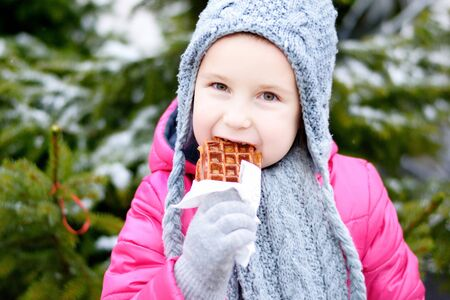 Adorable little girl eating warm waffle on cold winter day near Christmas tree