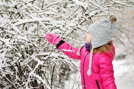 Funny little girl having fun in beautiful winter park