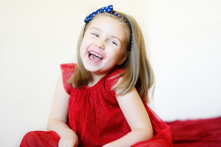 Portrait of a sweet laughing preschool girl in a red dress