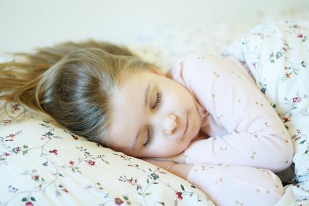 Adorable little girl sleeping in a warm bed Stok Fotoğraf