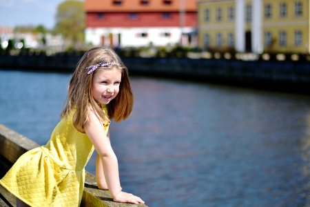 Adorable little girl playing by a river in sunny park on a beautiful summer day Stok Fotoğraf