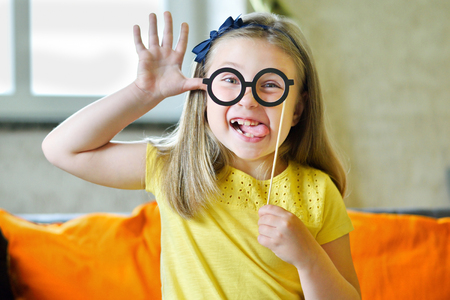 Little girl making face with funny glasses Stock Photo