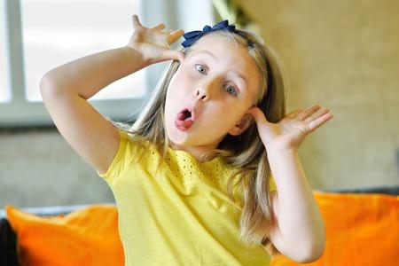 irrespeto: Pequeña muchacha adorable que hace la cara divertida y que muestra su lengüeta