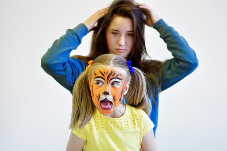 children party: Screaming girl with face painting of tiger and her mother