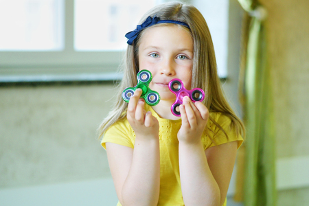 Little beautiful girl is playing with two spinners in hands