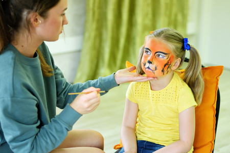 Adorable little girl getting her face painted like tiger