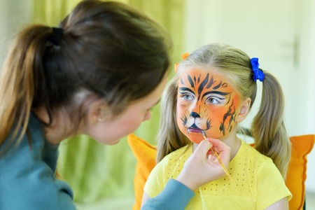 bodyart: Adorable little girl getting her face painted like tiger