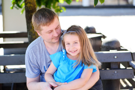 Father hugging daughter on the bench in the park on summer day